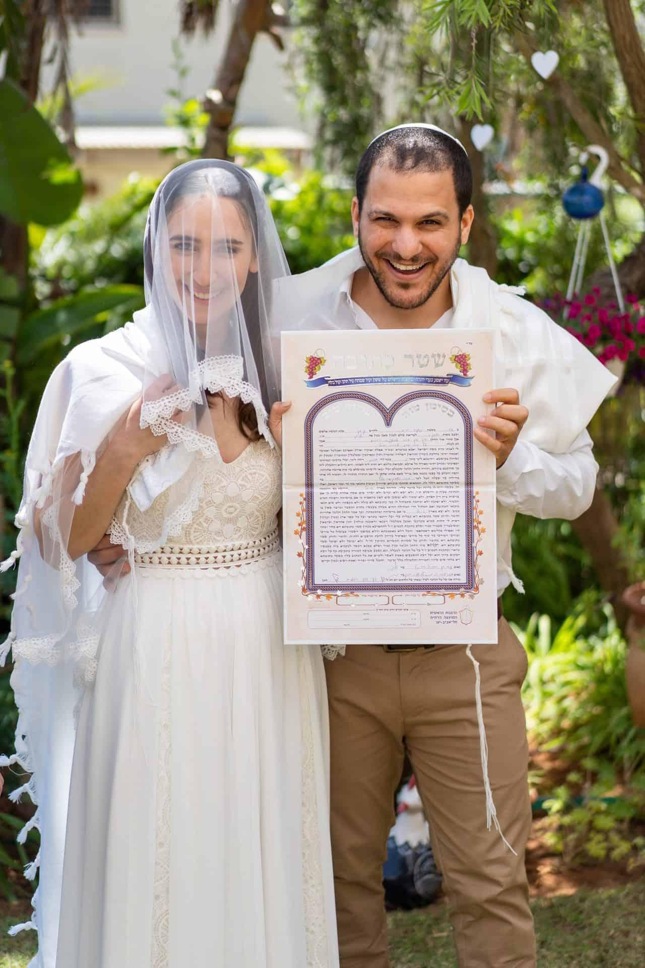 חתן וכלה מחזיקים כתובה